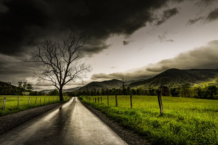 Dramatic Weather: Dusky sky over fields and a road after a rainstorm