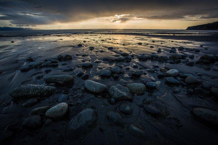 Coastal photography: dark-coloured rocks in shallow water at dusk