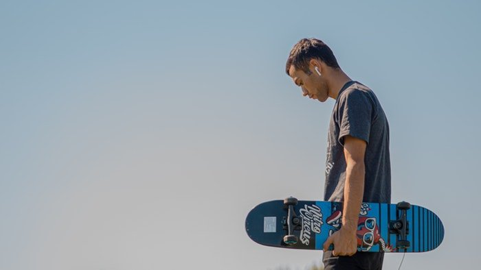 Man holding a skateboard against a blue sky