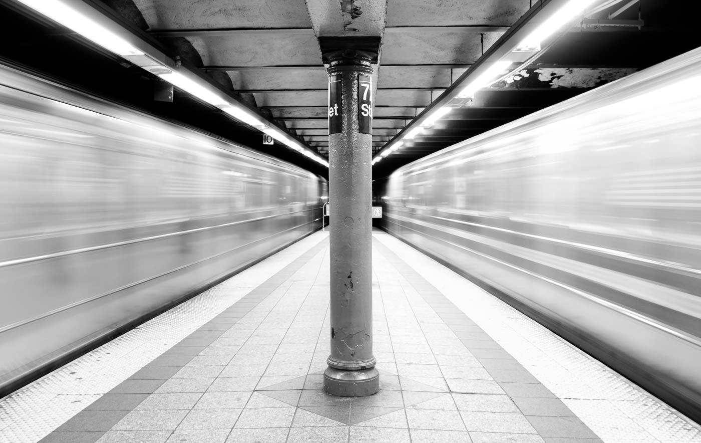 NYC Subway trains rushing by on both sides of platform, creating blurred space around the centre