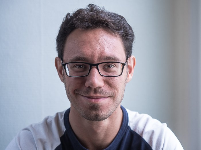 Portrait of man with glasses lit using split lighting with a reflector