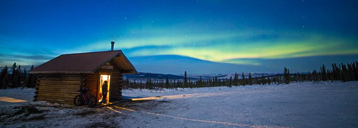 Picture of an Alaskan cabin with a view of the sky in the background.