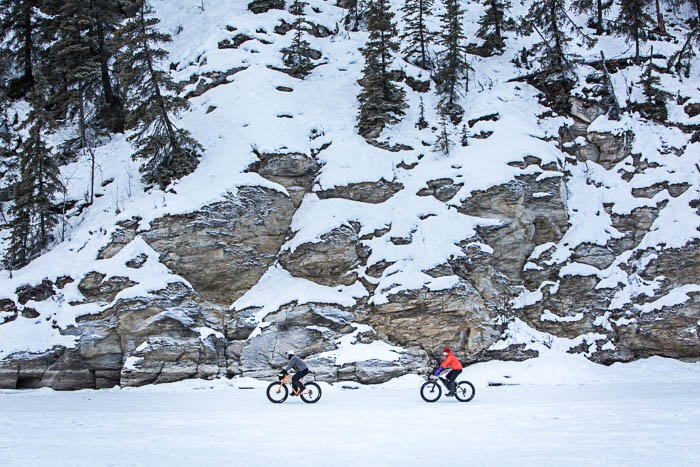 View from afar of two cyclists riding in the snow. The mountain side is in the background.