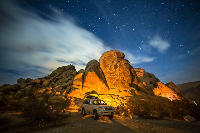 Picture at Joshua Tree National Park in California, showing a white car in front of tall rocks.