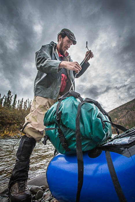 Low perspective photo of a man packing a raft.