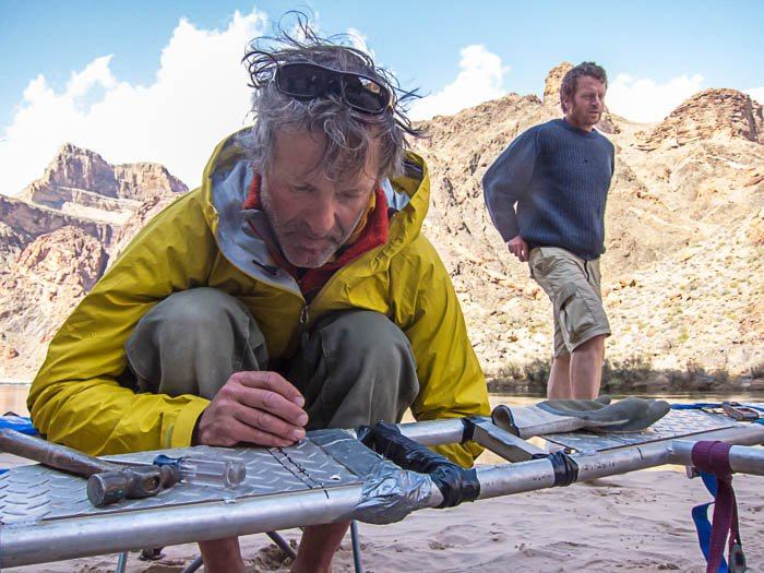 Adventure photography showing one man repairing a raft while another is standing in the background