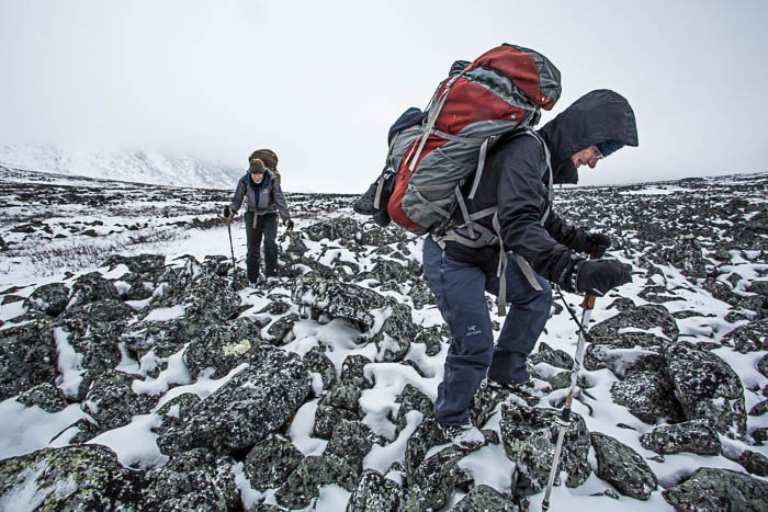 Two hikers with backpacks climbing a mountain in the snow.