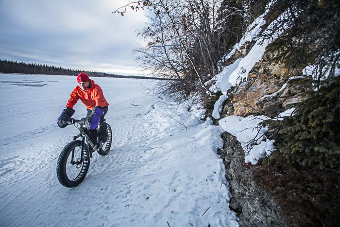 Adventure photography showing a man riding a fatbike in a winter landscape