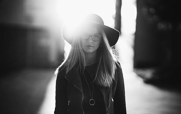 Greyscale portrait of a young woman wearing a hat and glasses.