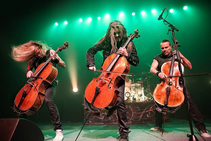 Apocalyptica backlit by green stage lights.