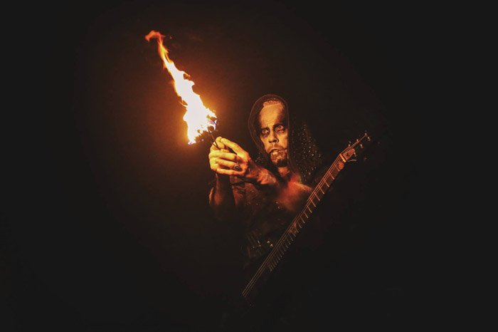 The front-man for Behemoth holding fire performance equipment.