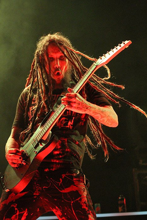 The KoRn guitarist front lit by red light against a green smoke background