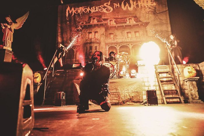 The lead singer for Motionless in White, with pyrotechnics disrupting the lighting.