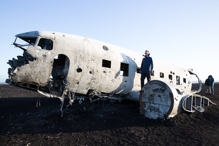 picture of man on the wing of an abandoned plane wreck, part of Iceland's Ghost Fleet