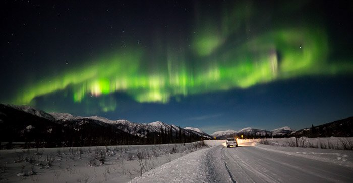 The Aurora over a settlement in the snowy fields of Alaska