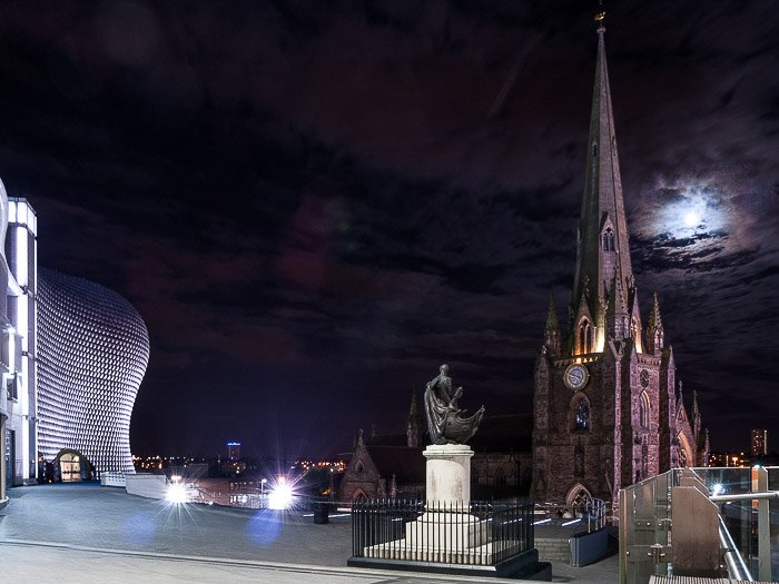 A picture of moon in the cloudy night sky over St Martin's Cathedral in Birmingham