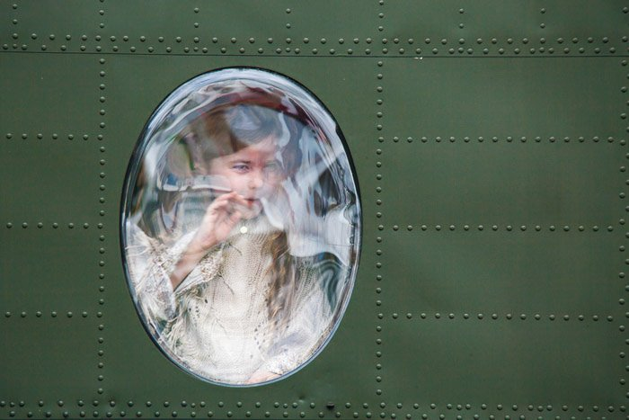 Young girl looking out the window of a military jet.