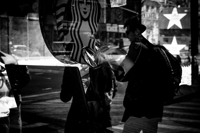 Black and white photograph of a Starbucks cafe with a couple overlaid on the customer inside. Double exposure effect reflection.