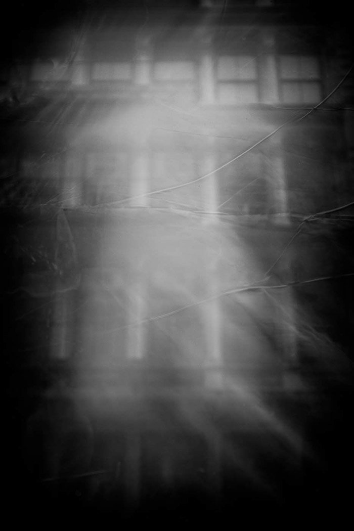 A ghostly haze is cast over the windows of a building in black and white street reflection photography.
