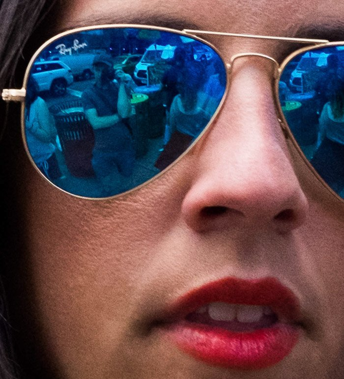 Reflection self-portrait in the lenses of a girl wearing blue polarized Ray Bans