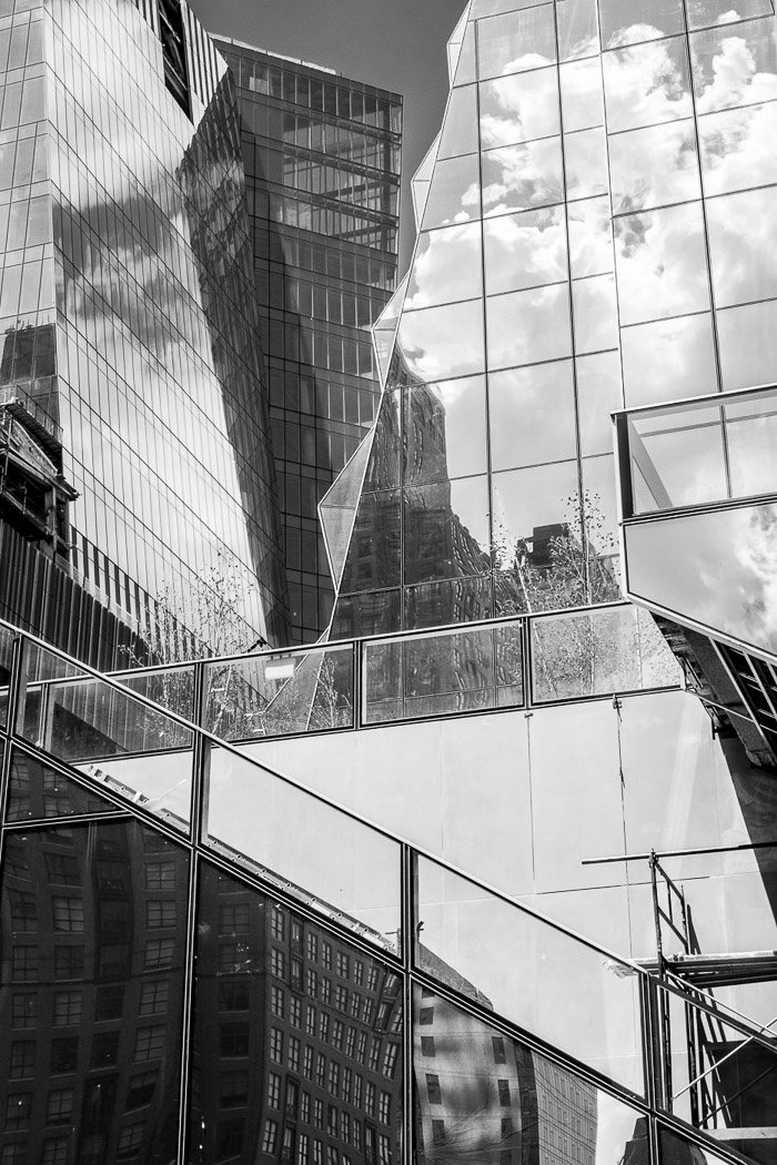 Glass-walled buildings create a stunning chain of reflections twisting contrasts and textures.