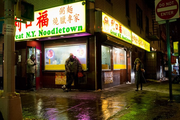 The reflections of the neon signs are visible in the rain-soaked streets creating a vibrant glow in the puddles.