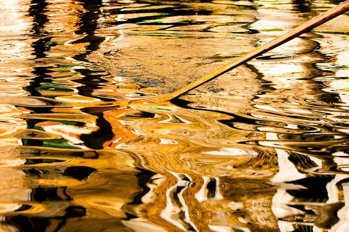 An oar breaking the surface of a river casting a choppy reflection. Night street photography in color.