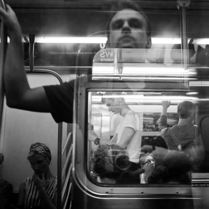 Self portrait reflection taken in subway overlaying reflection and image. Photographed in black and white monochrome.
