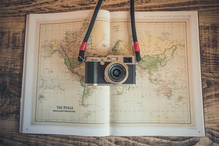 A flat lay photo of a film camera on a map