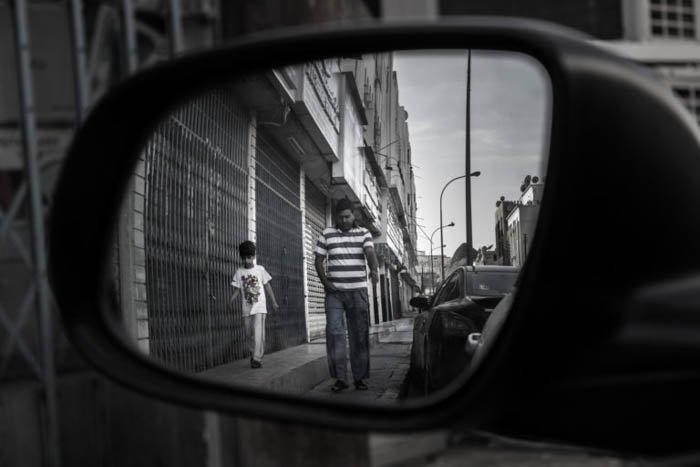 The reflection of a father and son walking down a street