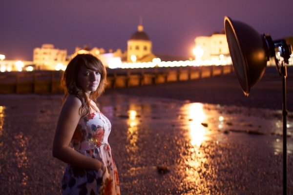 Portrait photography of a girl standing on a beach, harbour in background. Twilight photography.