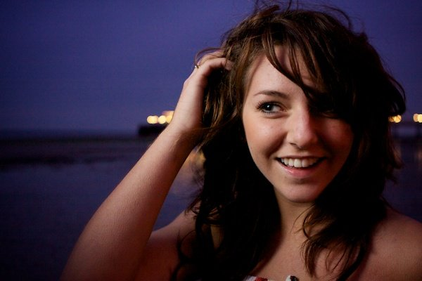 Close up portrait photography of a girl with her hands in her hair on a beach. Twilight photography.