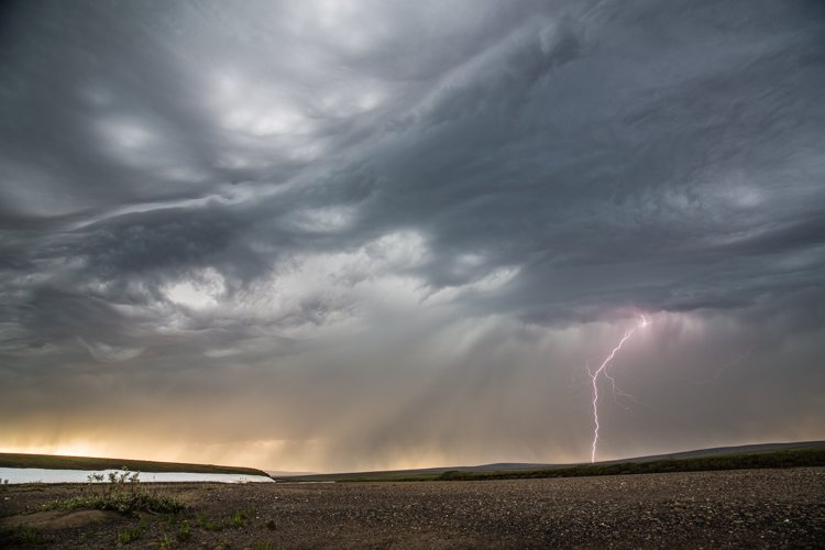 Snapshot of a lightning striking into a field in during a thunderstorm