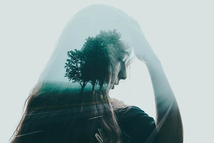 artistic photography of a young woman's self-portrait double exposed with a lone tree
