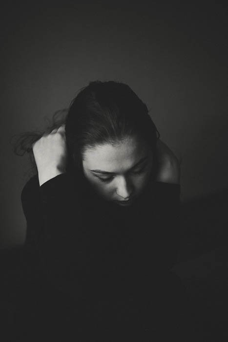 Atmospheric black and white portrait of a young woman hiding her head in her hands. Self portrait photography