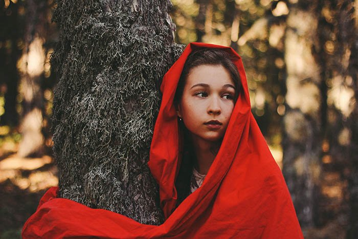 A fairytale inspired self portrait of a woman wearing a red hood, near a tree.