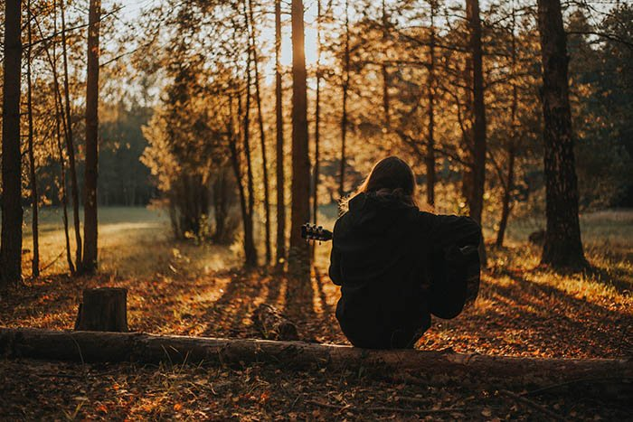 a girl playing guitar sitting on a log in a forest during fall. Creative self portrait photography