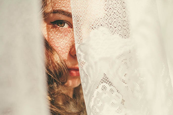 portrait of a girl hiding behind a white doily, only half of her face is visible