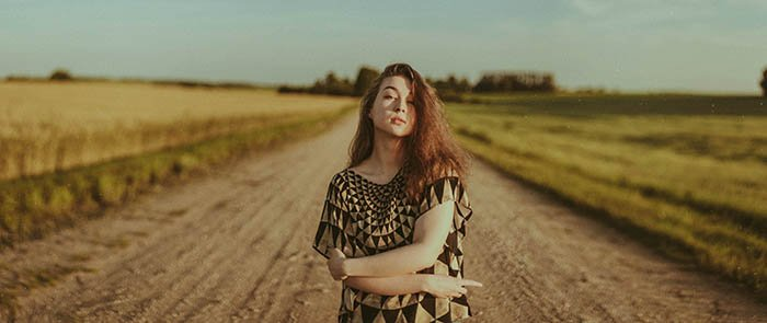 A self portrait picture of a redheaded woman standing on a road.