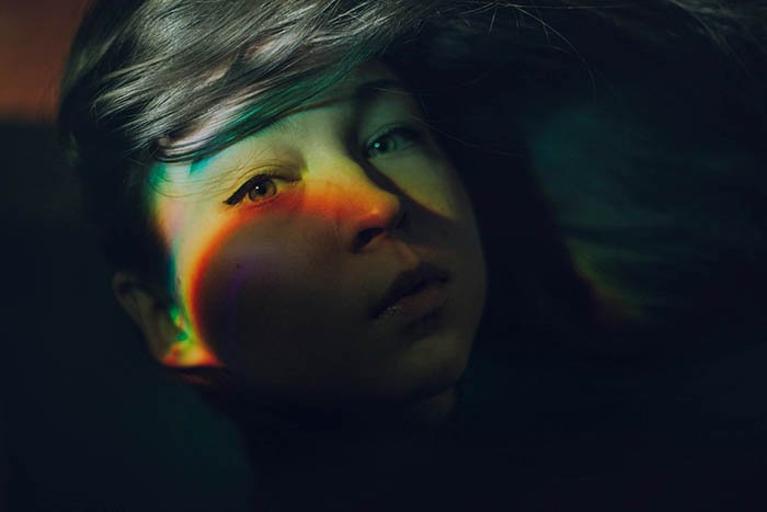 Mysterious self portrait photography showing rainbow effect on a girls face created with a CD