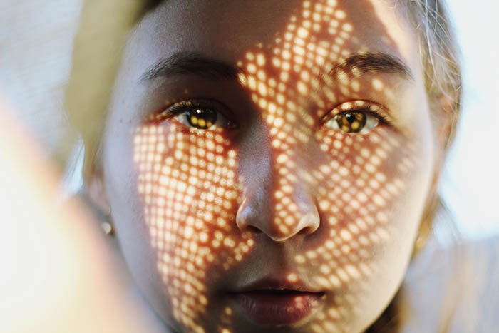 Self portrait photography close up of a woman's face covered by a shadowy pattern