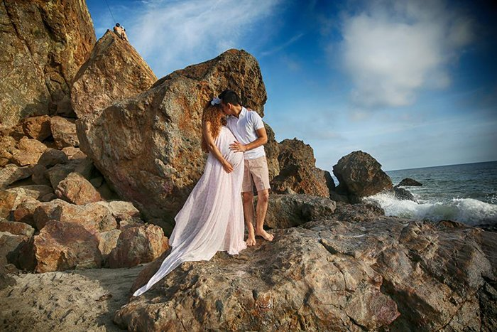 Photo of a pregnant couple standing on rock formations by the beach. The woman is wearing a long pink dress and they are embracing.