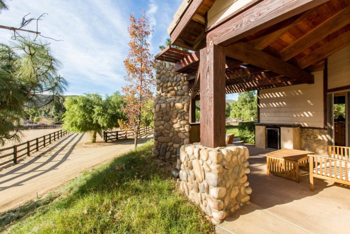 Real estate photography depicting the front porch of a house and the road leading up to it