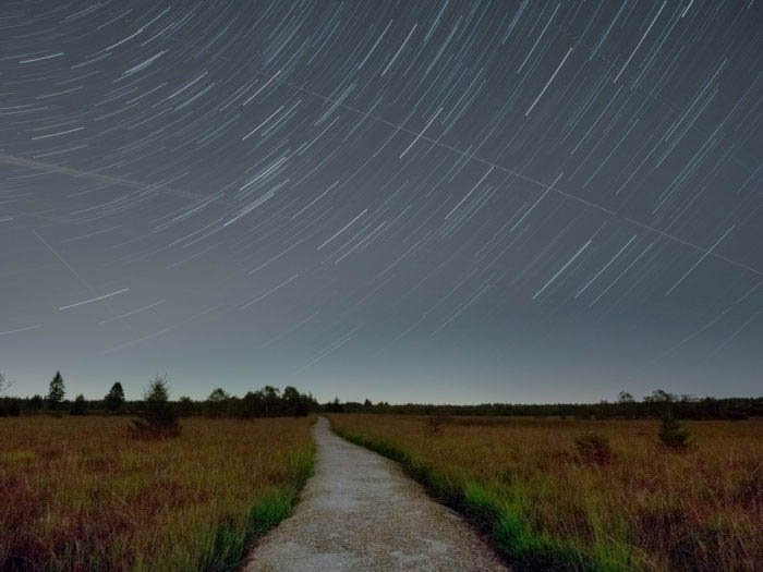 star trails photography over the high fens plateau in Belgium, with a road in the foreground