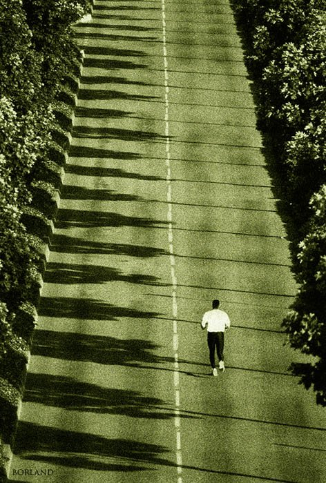 man running down an empty road - aerial photography