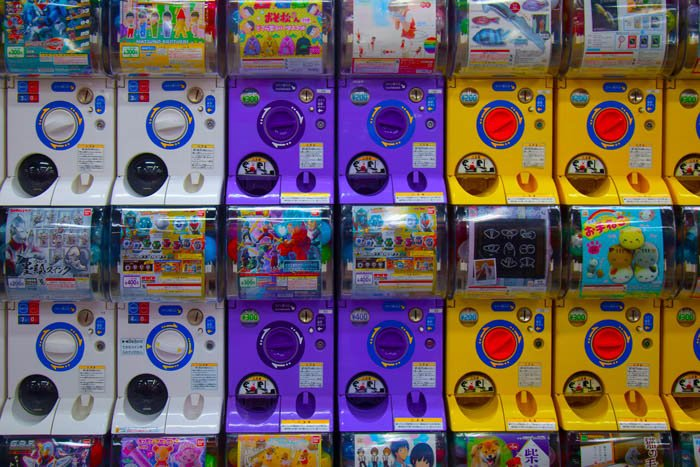 Japanese toy dispensers arranged by colour in a pattern: white, purple, yellow