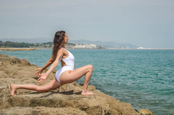 Yogini performing yoga pose on the beach, overlooking the sea