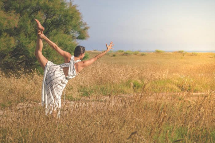 Girl wearing a white dress performing dancer's pose in a field of wheat