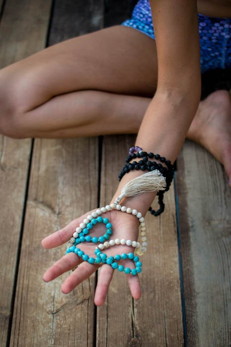 Close-up photo of mala beads in a female model's hand