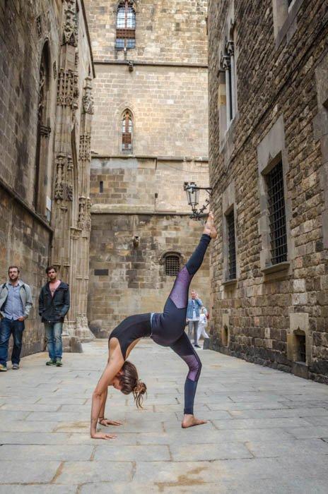 girl performing one-legged yoga wheel pose on the street